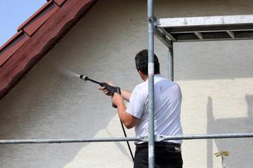 Robotnik, malarz myje karcherem ścianę, fasade budynku mieszkalnego stojąc na rusztowaniu.
