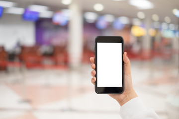 A woman hand holding smart phone device in the airport check-in background.