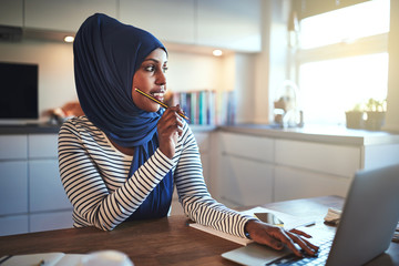 Young Arabic female entrepreneur thinking while working in her k