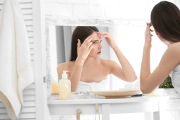 Teenage girl with acne problem looking in mirror indoors