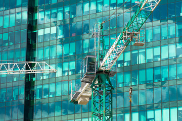 Construction crane on building skyscraper apartment house, on a background of glass texture of financial offices windows.