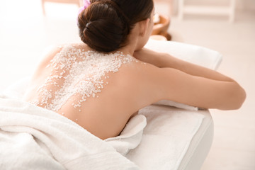 Beautiful young woman with body scrub on her back in spa salon