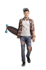 Teenage skater with a longboard walking towards the camera