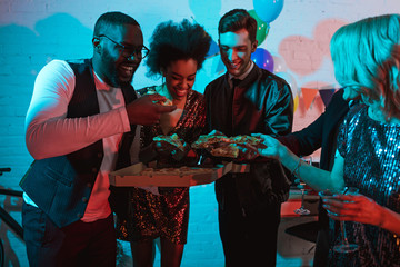 Young men and women eating pizza and holding drinks at party