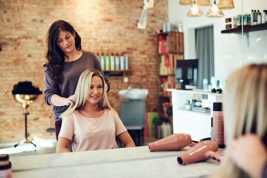 Smiling woman discussing her hair with a salon stylist