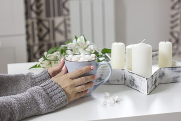 Cocoa with marshmallows in female hands on white background flowers, candles, details of modern interior