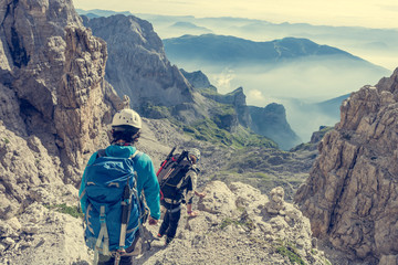 Pair of mountaineers walking a mountain path.