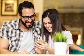 Couple of office workers, bearded man in eyeglasses and brunette girl having fun watching taked pictures on smartphone