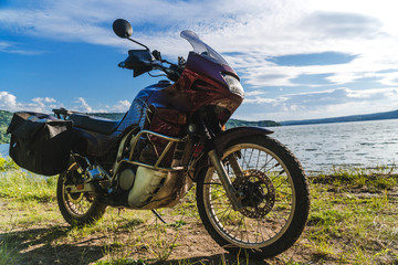 Motorcycle at sunset at lake. off road touring adventure travel enduro active lifestyle