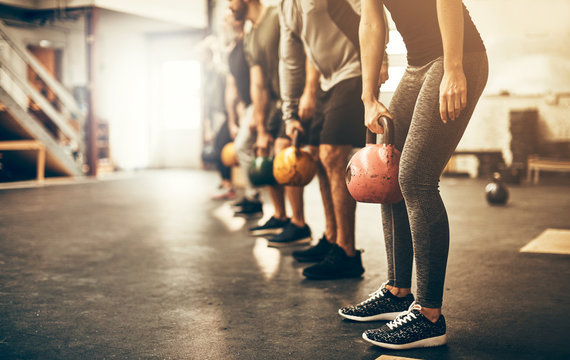 People lifting dumbbells together during a gym workout class
