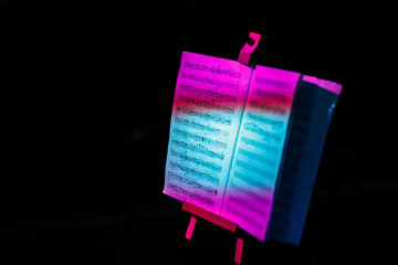 sheet music on the music stand at the scene in the colorful light beams