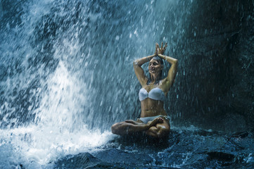 attractive woman sitting at rock in yoga pose for spiritual relaxation serenity and meditation at...