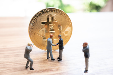Miniature. Businessman handshake successful agreement with bitcoin