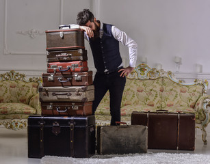 Move out and relocation concept. Macho elegant on tired face, exhausted at end of packing, leans on pile of vintage suitcases. Man with beard and mustache packed luggage, white interior background.