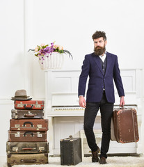 Macho attractive, elegant on strict face carries vintage suitcases. Butler and service concept. Man with beard and mustache wearing classic suit delivers luggage, luxury white interior background.