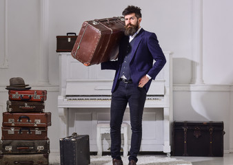 Man, traveller with beard and mustache with baggage, luxury white interior background. Macho stylish on strict face stands and carries big vintage suitcase. Baggage and travelling concept.