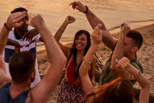 Hilarious excited young multiethnic friends dancing and laughing loudly while having fun at beach party