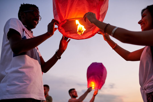 Cheerful excited young interracial couple holding Chinese lantern with burning candle inside of it and making wish to be always together outdoors