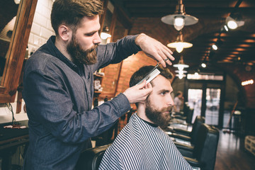 Another picture of bearded guys in barbershop. One man is cutting hair of another man. The procedure is very long but intensive.