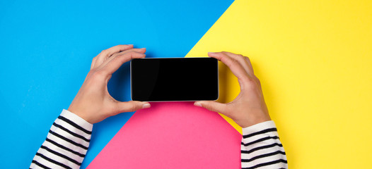 Woman's hands with smartphone on colorful background.
