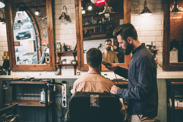 Nice pictur is a barber shop. Two guys are there. One of them is cutting hair with electrical razer while the other one is sitting in chair.