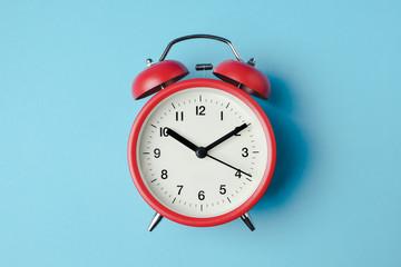 Red vintage alarm clock on light blue color background Wall mural
