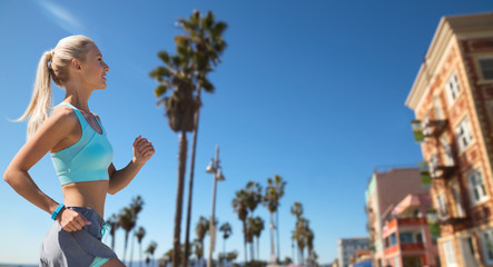 sport and healthy lifestyle concept - smiling young woman with fitness tracker running over venice beach background in california