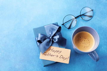 Morning cup of coffee, gift box and eyeglasses on blue table for breakfast on Happy Fathers Day.