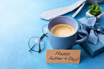 Happy Fathers Day card, cup of coffee, gift box and eyeglasses on blue table for breakfast.