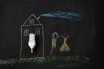 energy saving light bulb and chalk child's drawing of the house and people
