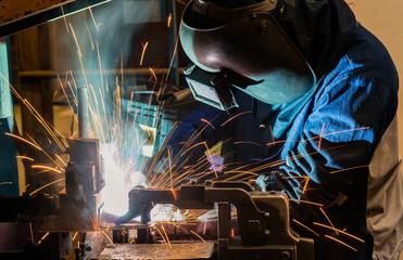 Industrial worker is welding in factory