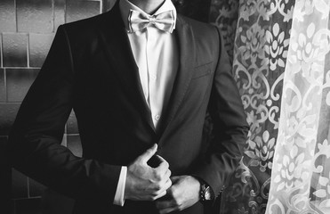 Handsome groom in white shirt is wearing the bow tie and suit near the window. Wedding day details. Man portrait photoshoot. Black and white.