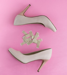 Pair of nude high heels with plasters in between on a pink backround.