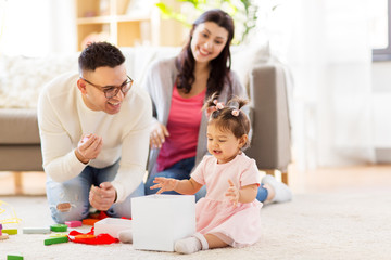 family, holidays and people concept - mother, father and happy little daughter with gift box at home birthday party