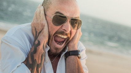 screaming hipster MAN shirtless with tattoos and beard on a sandy and windy beach in spain