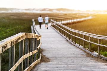 senior  elderly couple in footbridge walking to sunset