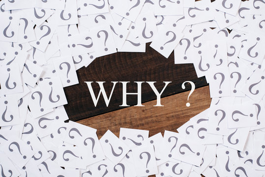 white paper note with question mark and WHY word in the center on wooden table. WHY concept background