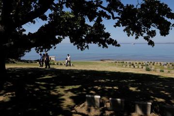 Visitors walk between the tombstones of Australian soldiers at the Ariburnu Memorial in Anzac Cove in Gallipoli
