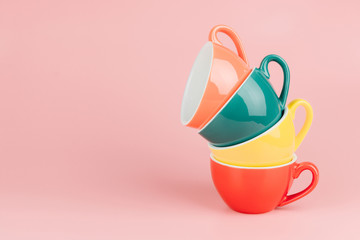 Colorful stack of cups for latte coffee in a vintage pastel colored tone on pink background with copy space.