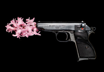 A hand gun launches a hyacinth flower isolated on black background