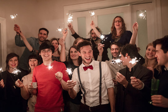 Group of friends using sparklers at party
