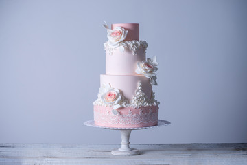 Beautiful elegant four tiered pink wedding cake decorated with roses flowers. Concept floral from sugar mastic