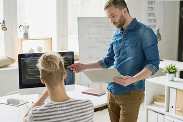 Serious confident bearded software engineer with tablet giving advice to programmer and explaining mistakes while pointing at monitor in office