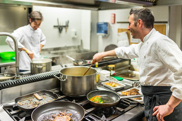 Chef and cook at work in a restaurant kitchen