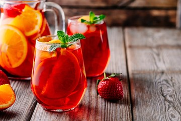 Homemade red wine sangria with orange, apple, strawberry and ice in glass and pitcher on wooden background.