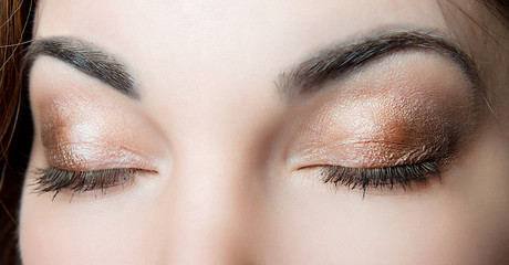 Professional make-up on closed eyes of a close-up girl on a black background. Female make-up.