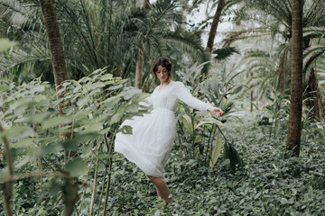 Romantic woman in white spinning in green woods