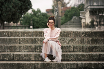Stylish woman in skirt sitting on steps