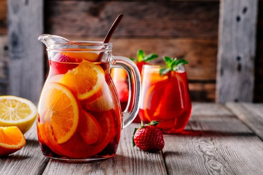 Homemade red wine sangria with orange, apple, strawberry and ice in pitcher  and glass on wooden background