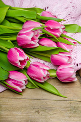 Pink tulip bouquet on retro wooden background, copy space